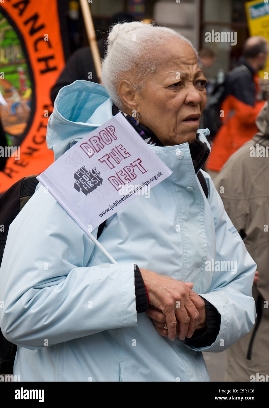 Old worman with a 'Drop the debt' flag at G20 March in Picadilly, London on 28th March 2009 - Stock Image