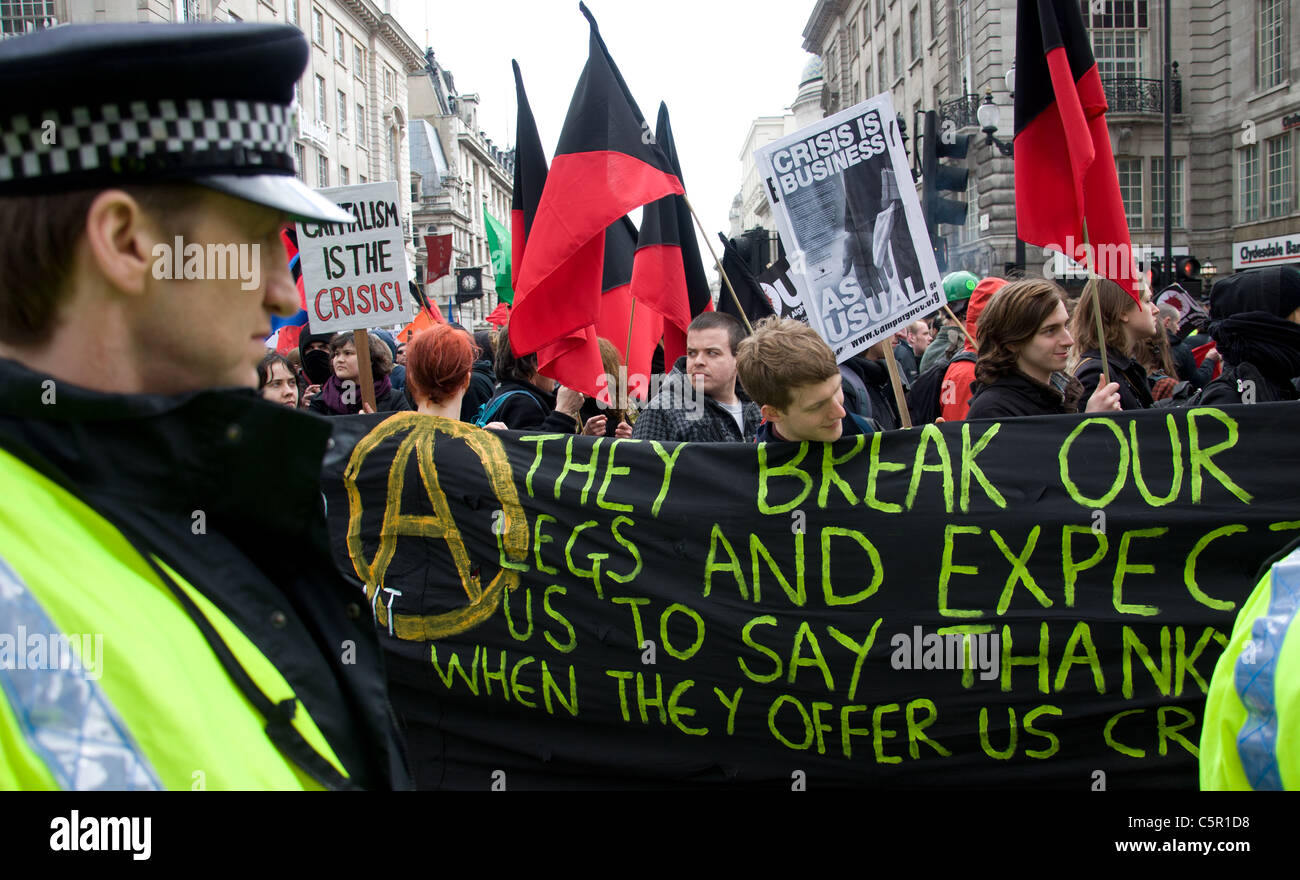 Anarchist flags and anarchists with a large banner at G20 March in London on 28th March 2009 - Stock Image