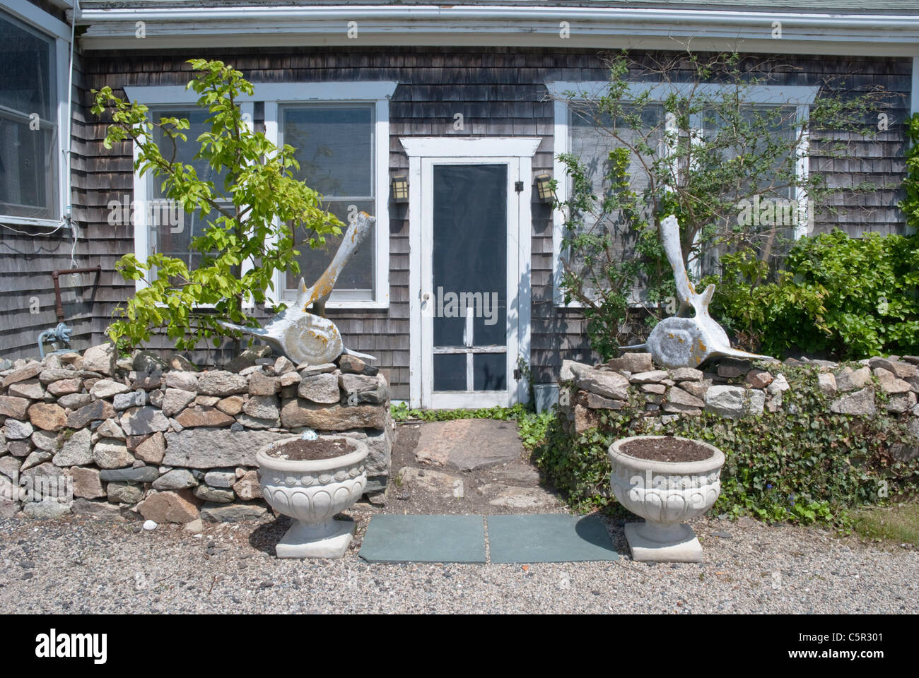 Whale vertebrae make interesting conversation pieces in front of an historic home in old Westport, Massachusetts. - Stock Image