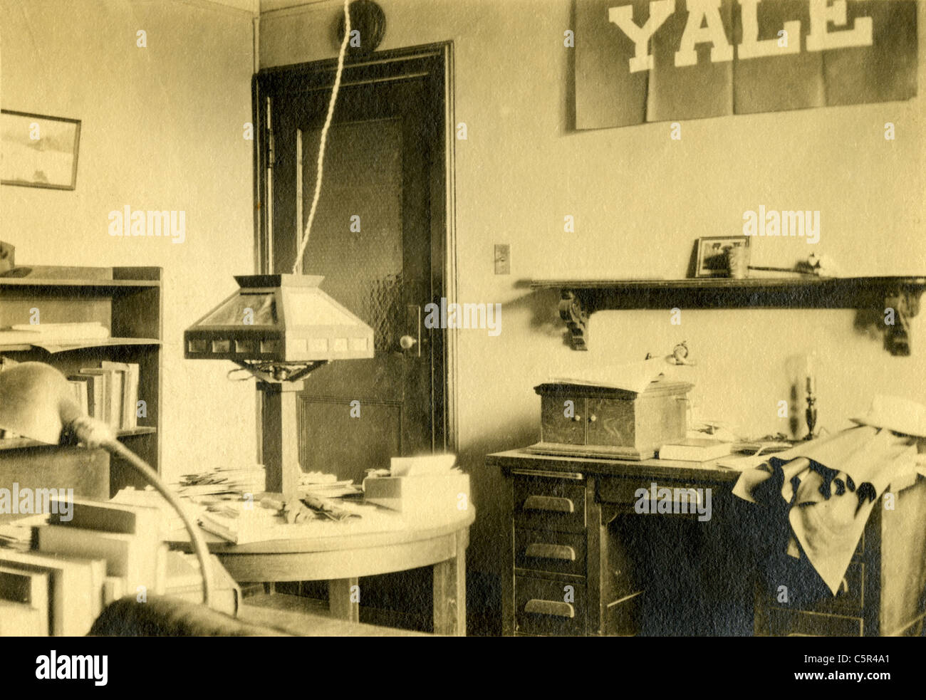 Circa 1910s photograph of an old room or office with a Yale University banner and Mission style electric lamp. - Stock Image