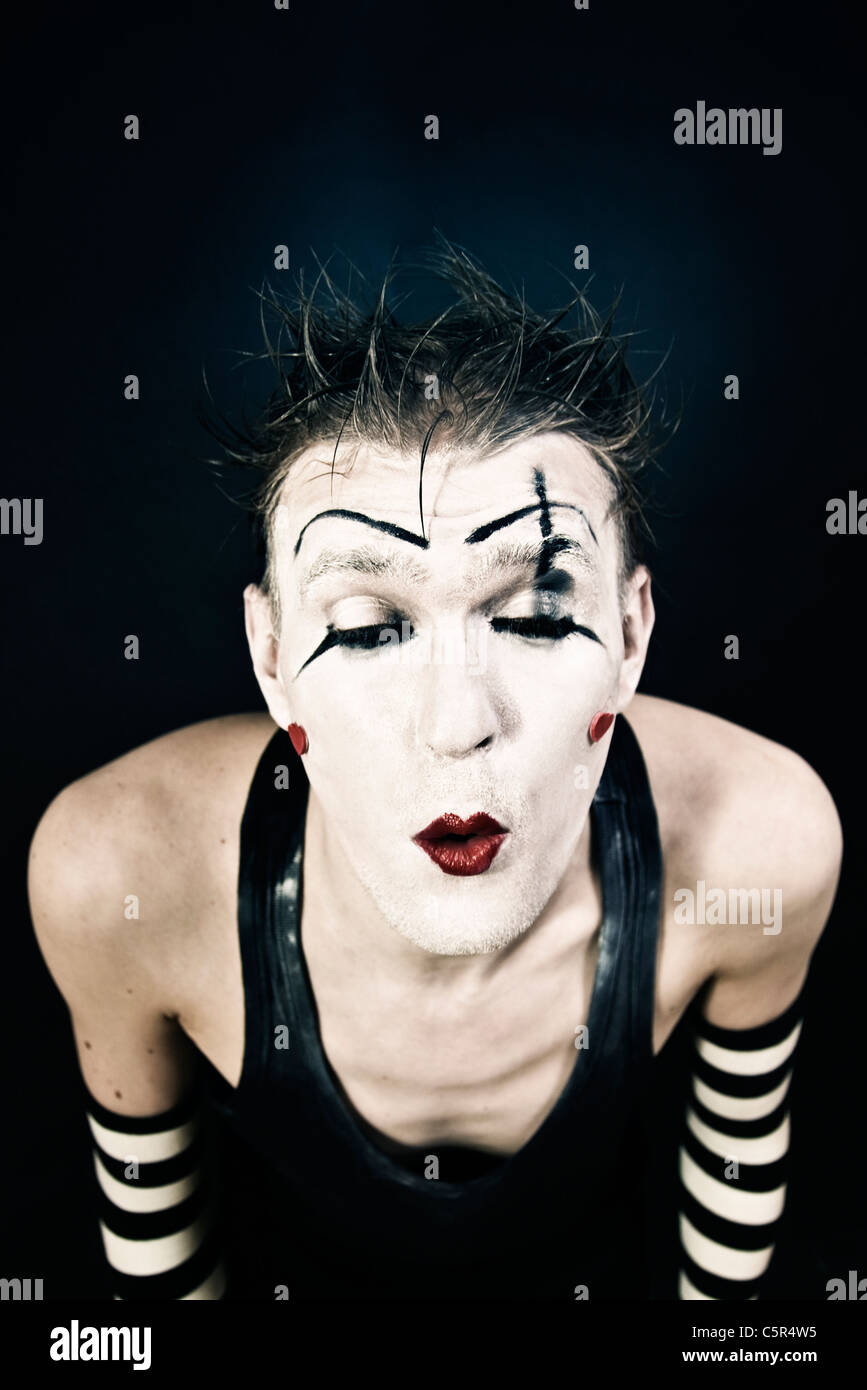 Studio portrait of a terrible clown with a dark makeup on black background Stock Photo
