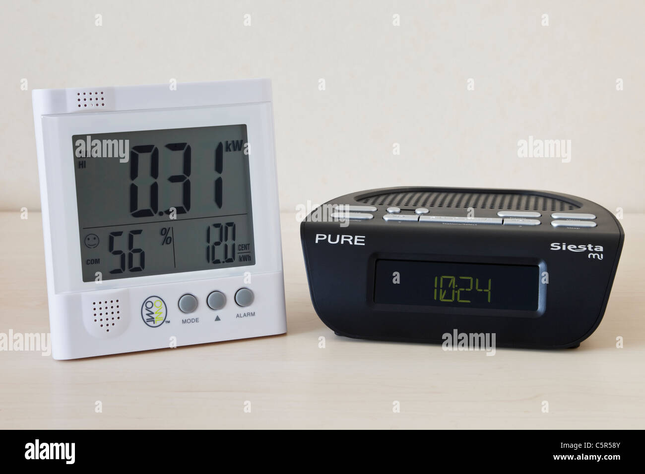 DAB digital alarm clock radio and Owl wireless LED electricity monitor showing kilowatts of electricity being used - Stock Image