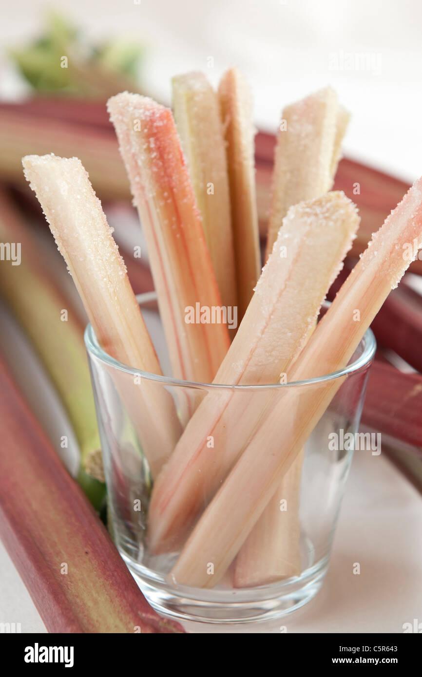 Fresh raw rhubarb sticks with sugar as an appetizer - Stock Image