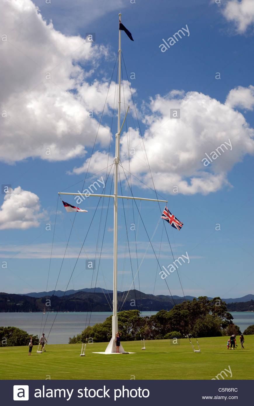 tourists at flagpole on the lawn of Waitangi - Stock Image