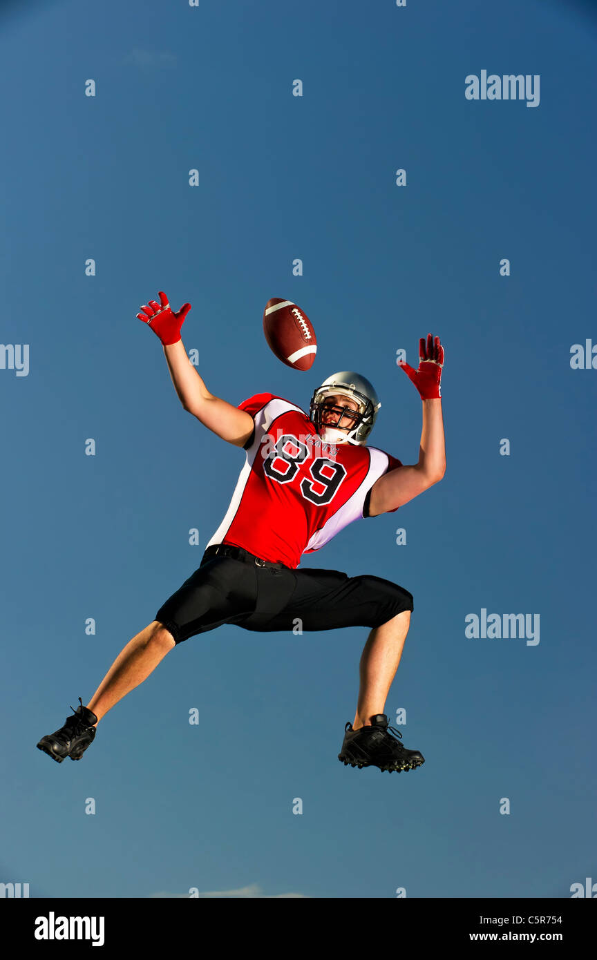 American Football player leaps to make catch. - Stock Image
