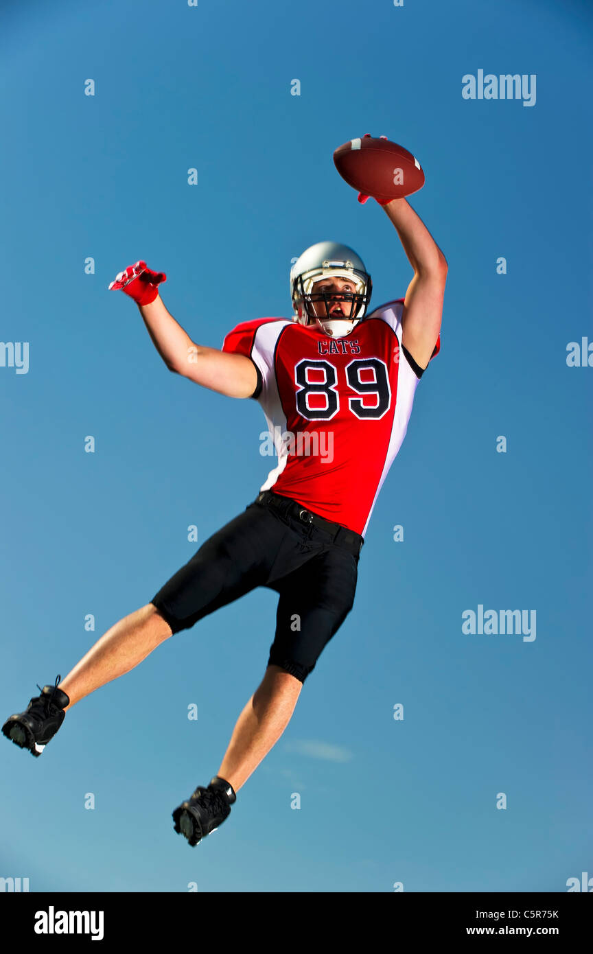 American Football player jumps high to make the catch. - Stock Image