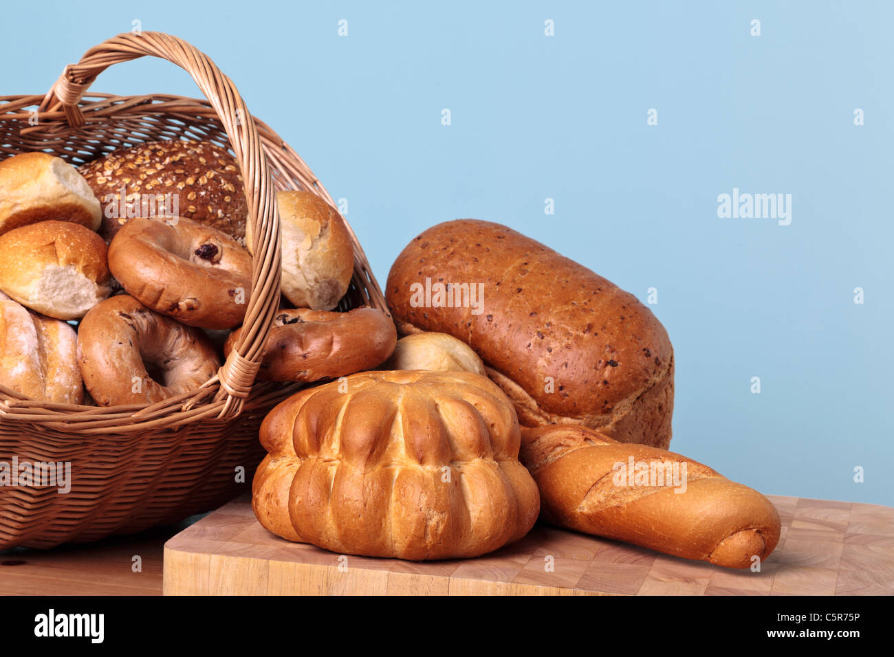 Photo of different types of bread spilling out from a basket. - Stock Image