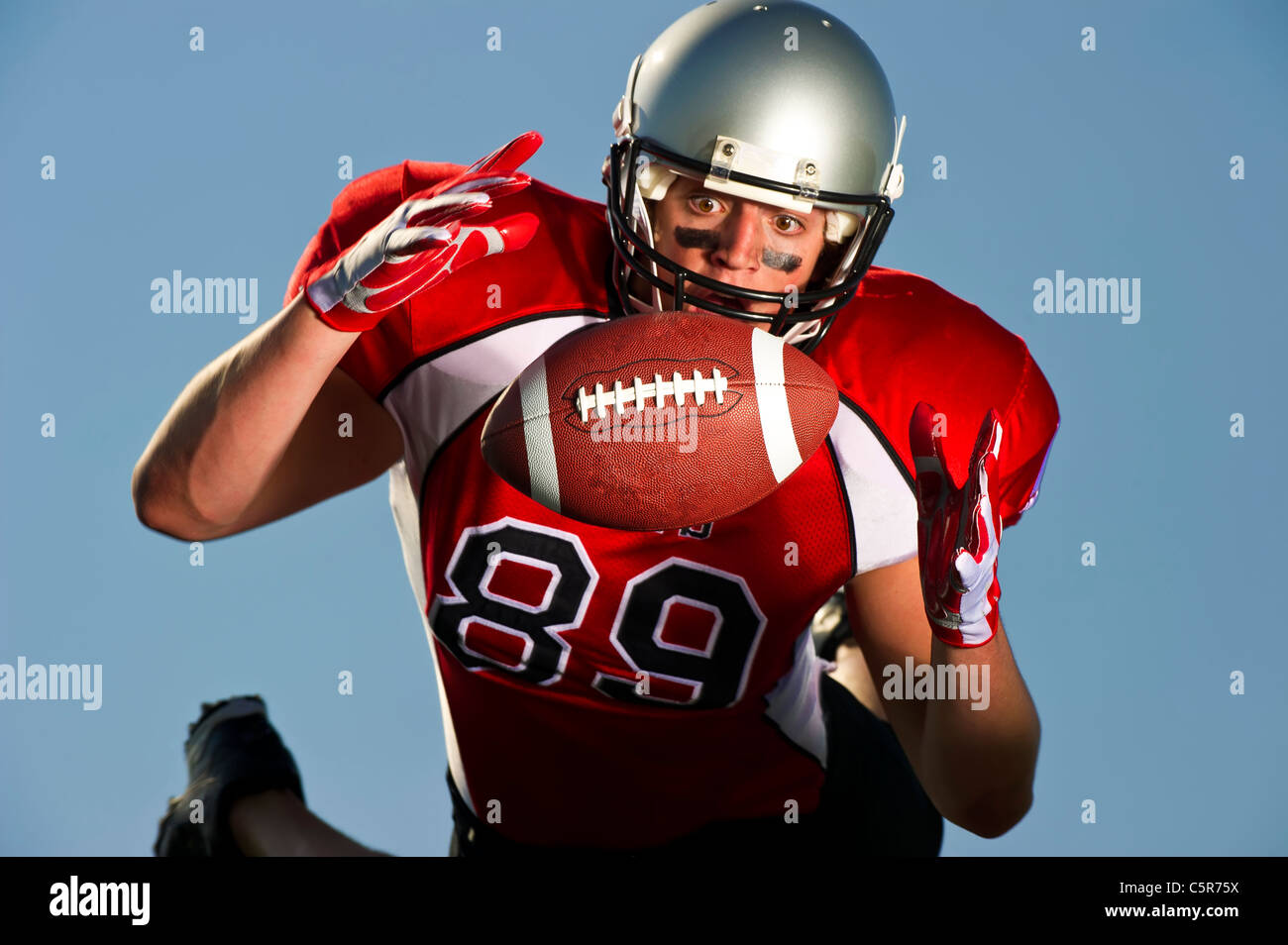 American Football player focused on making the catch. - Stock Image