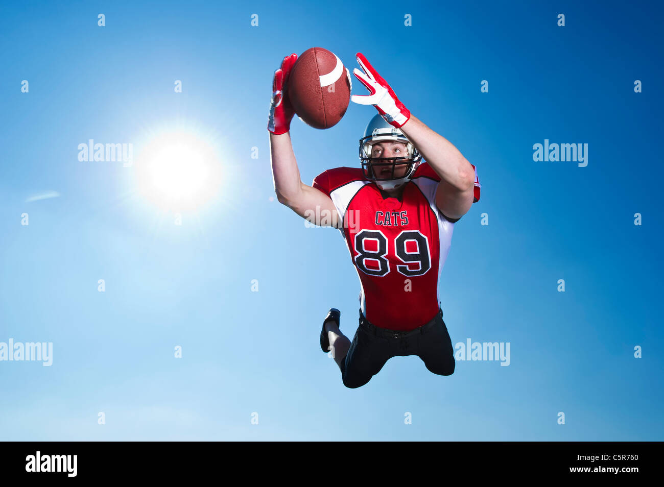 American Footballer focused on ball to make the catch. - Stock Image