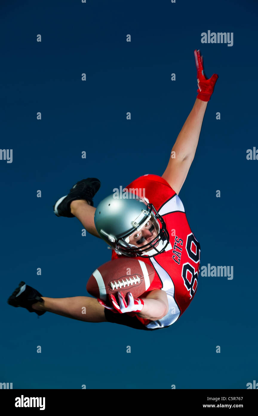 American Footballer flying through the air to make the catch. - Stock Image