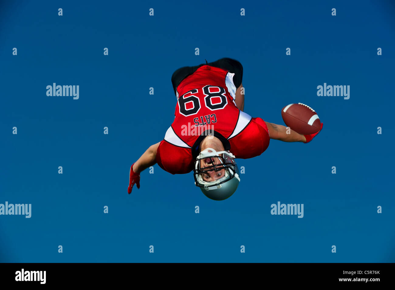 American Footballer celebrates touchdown and back flips with the ball. - Stock Image