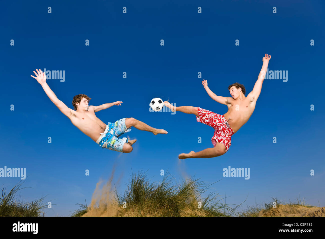Two players playing beach soccer compete for the ball. - Stock Image