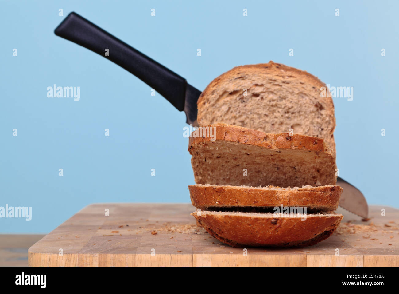 Photo of a wholemeal loaf of bread being sliced with a knife. - Stock Image
