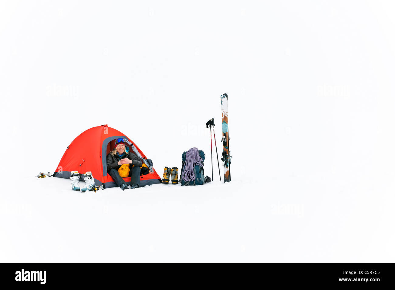 A happy camper camping on snow. - Stock Image
