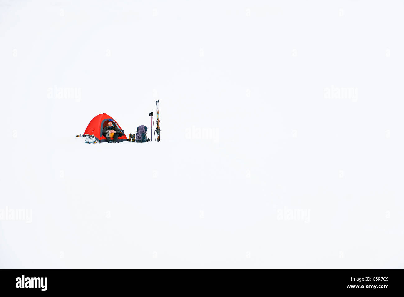A skier camping in deep snow. - Stock Image