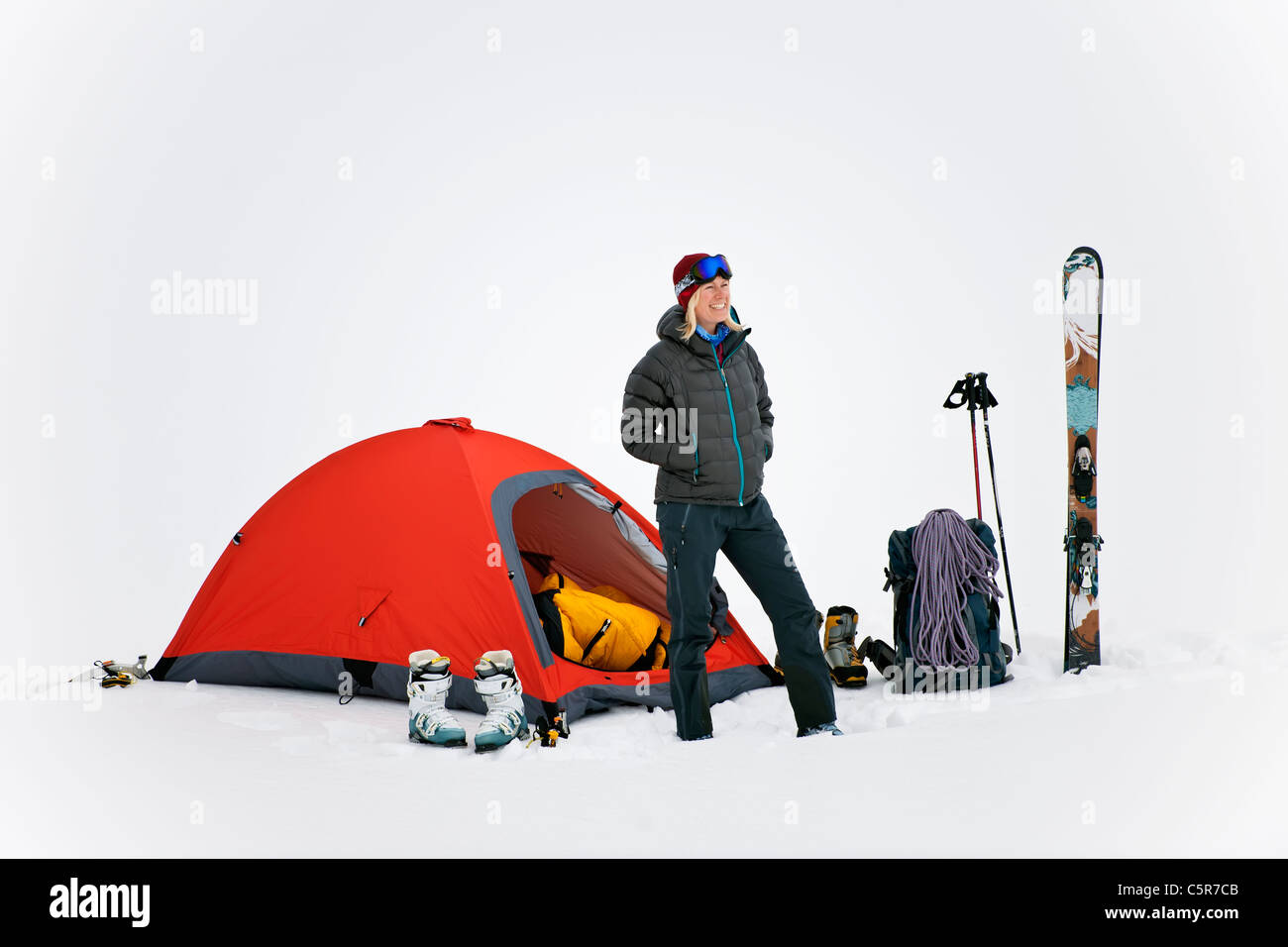 A woman camping in deep snow - Stock Image
