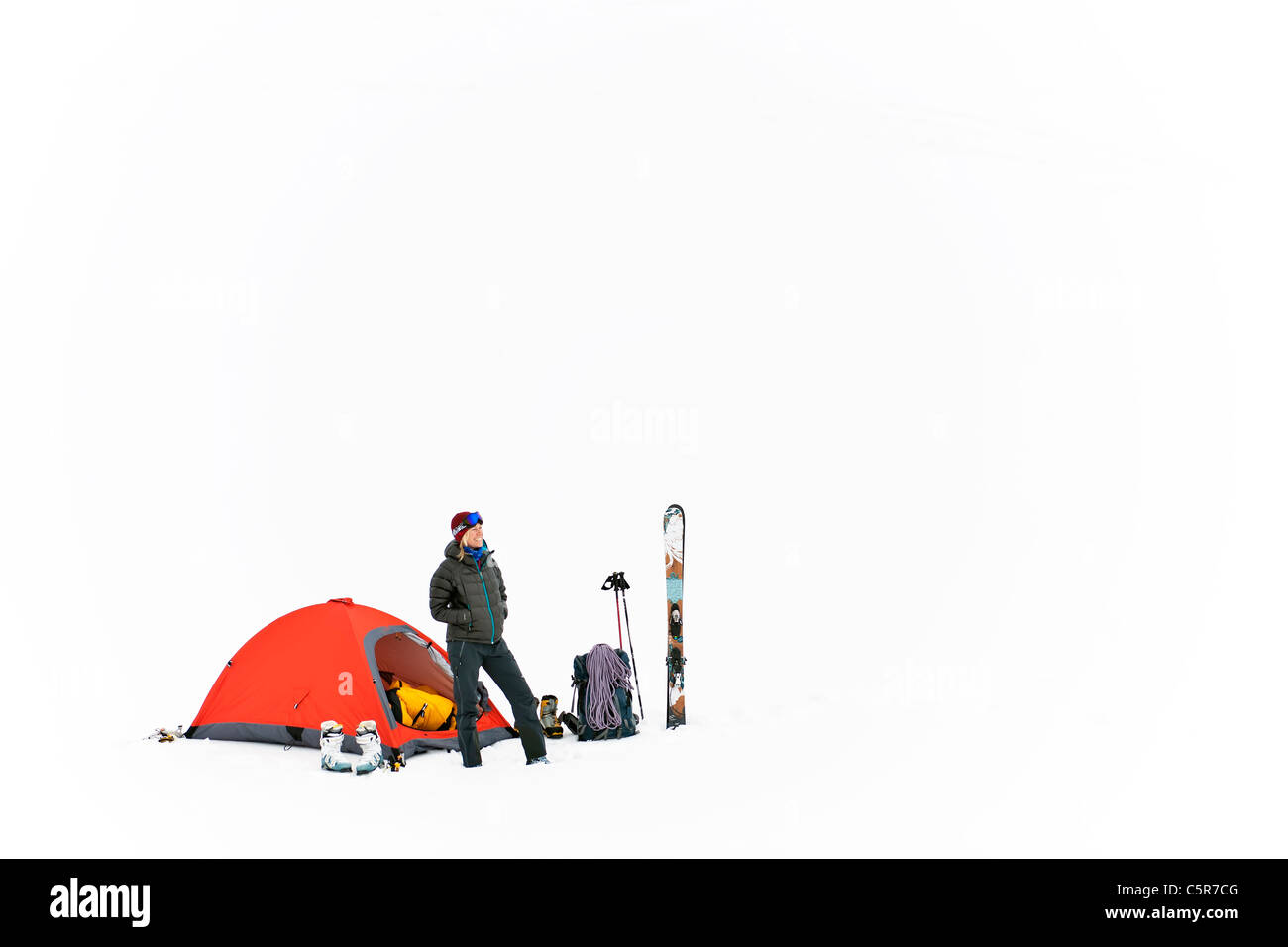 A smiling happy mountaineer with all her equipment at base camp. - Stock Image