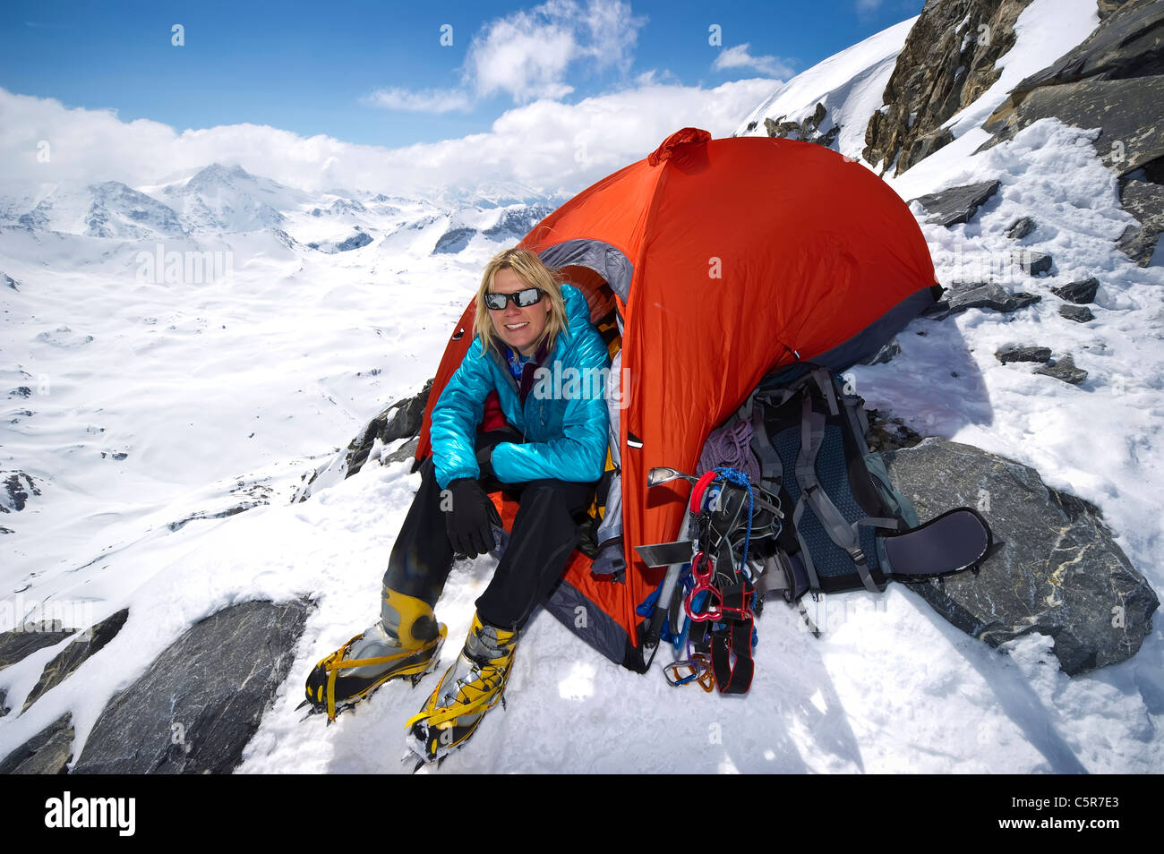 A mountaineer sitting in tent on high on high snowy mountains. - Stock Image