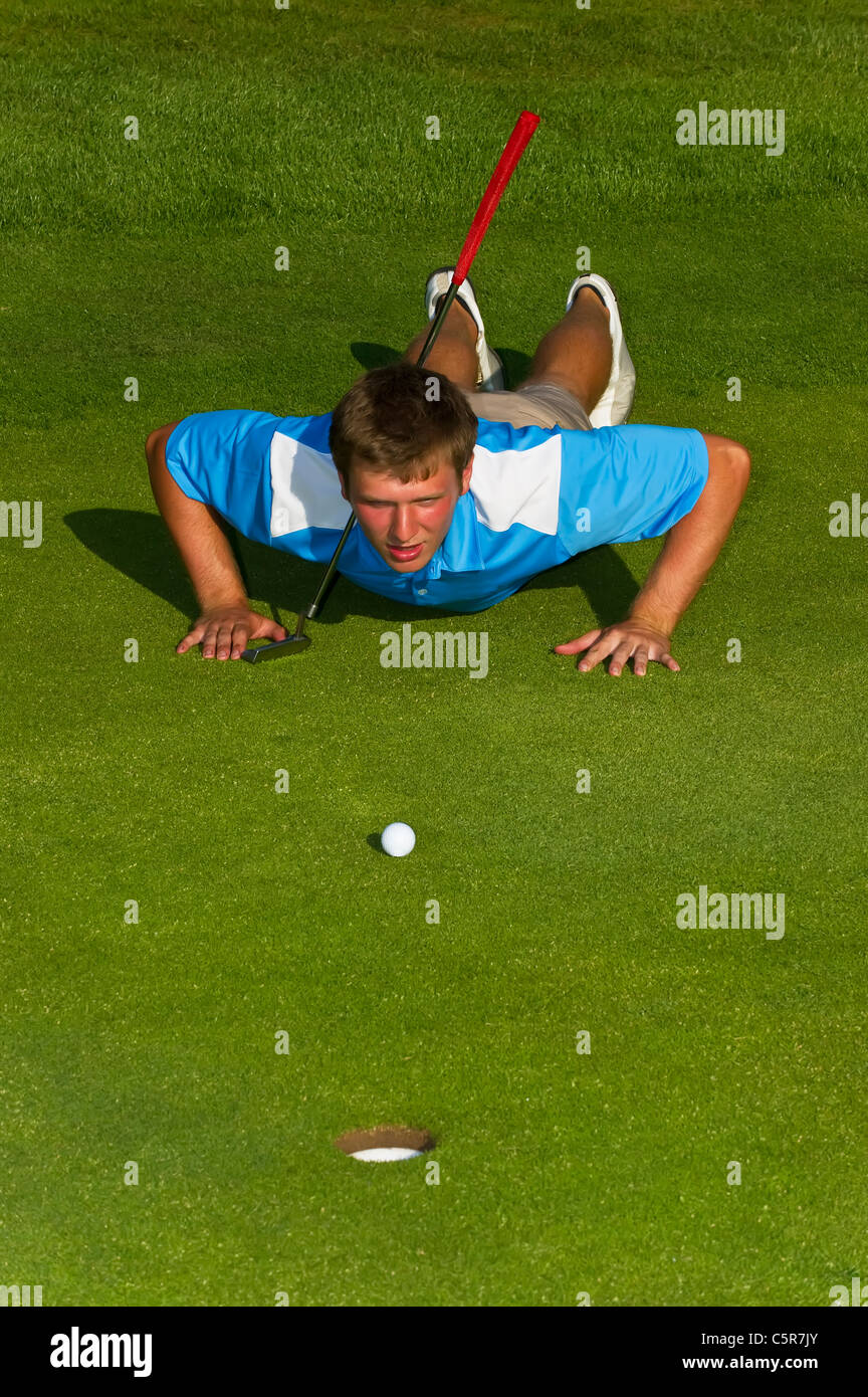 A golfer lining up a put on the green. - Stock Image