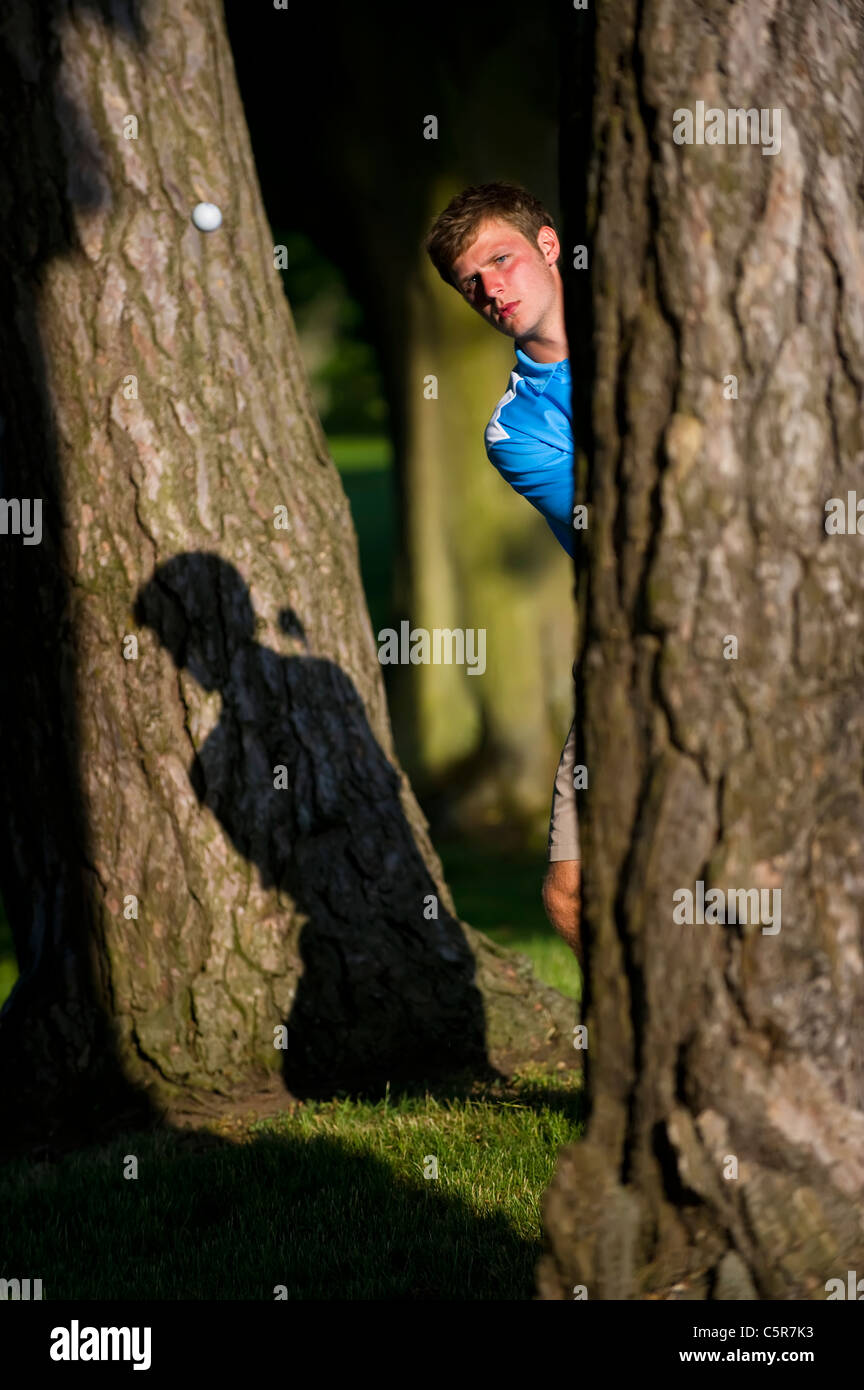A golfer playing a shot out of the trees focused on the ball. - Stock Image