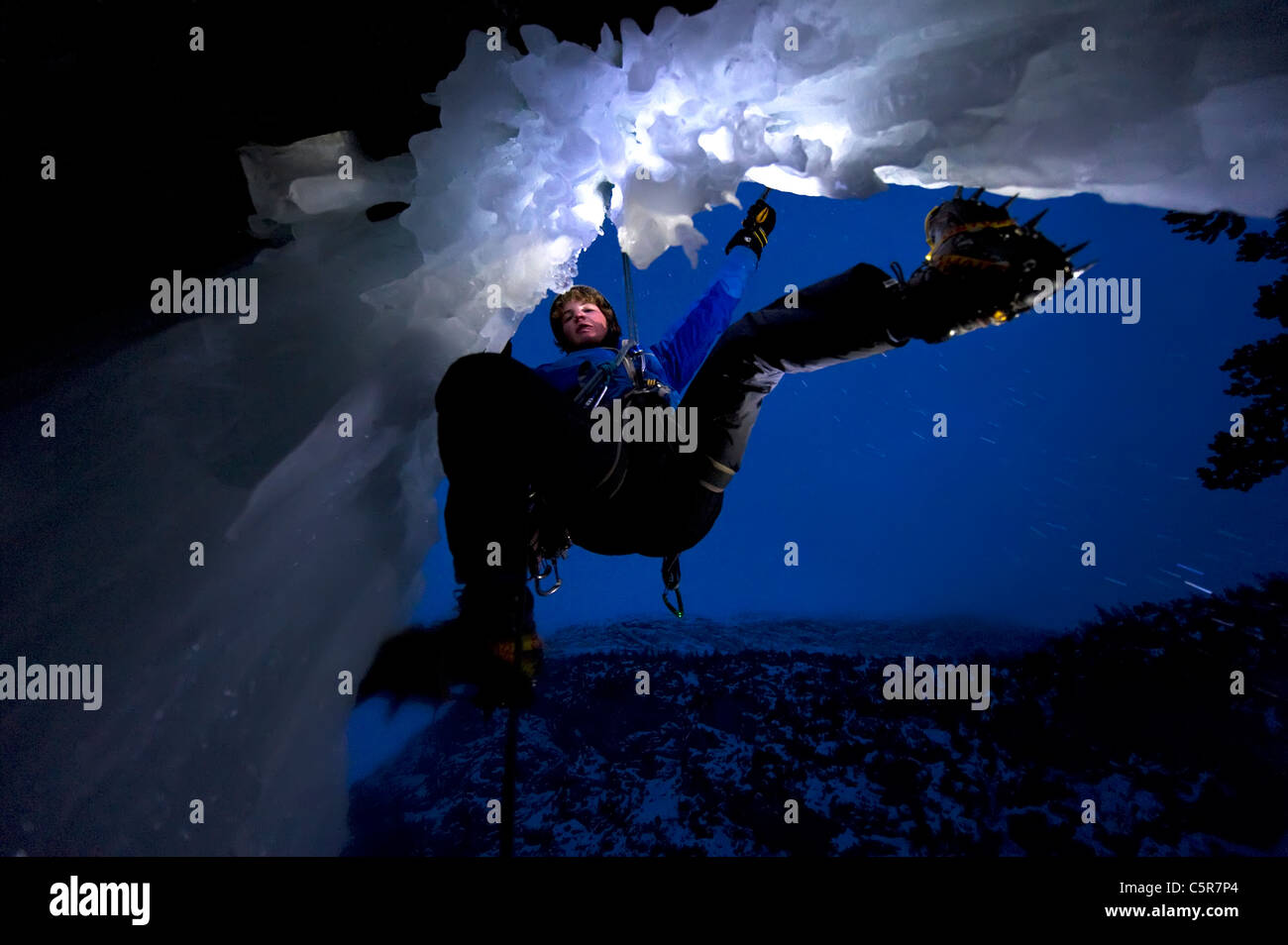 Ice Climbing at night on the edge of a cave. Stock Photo