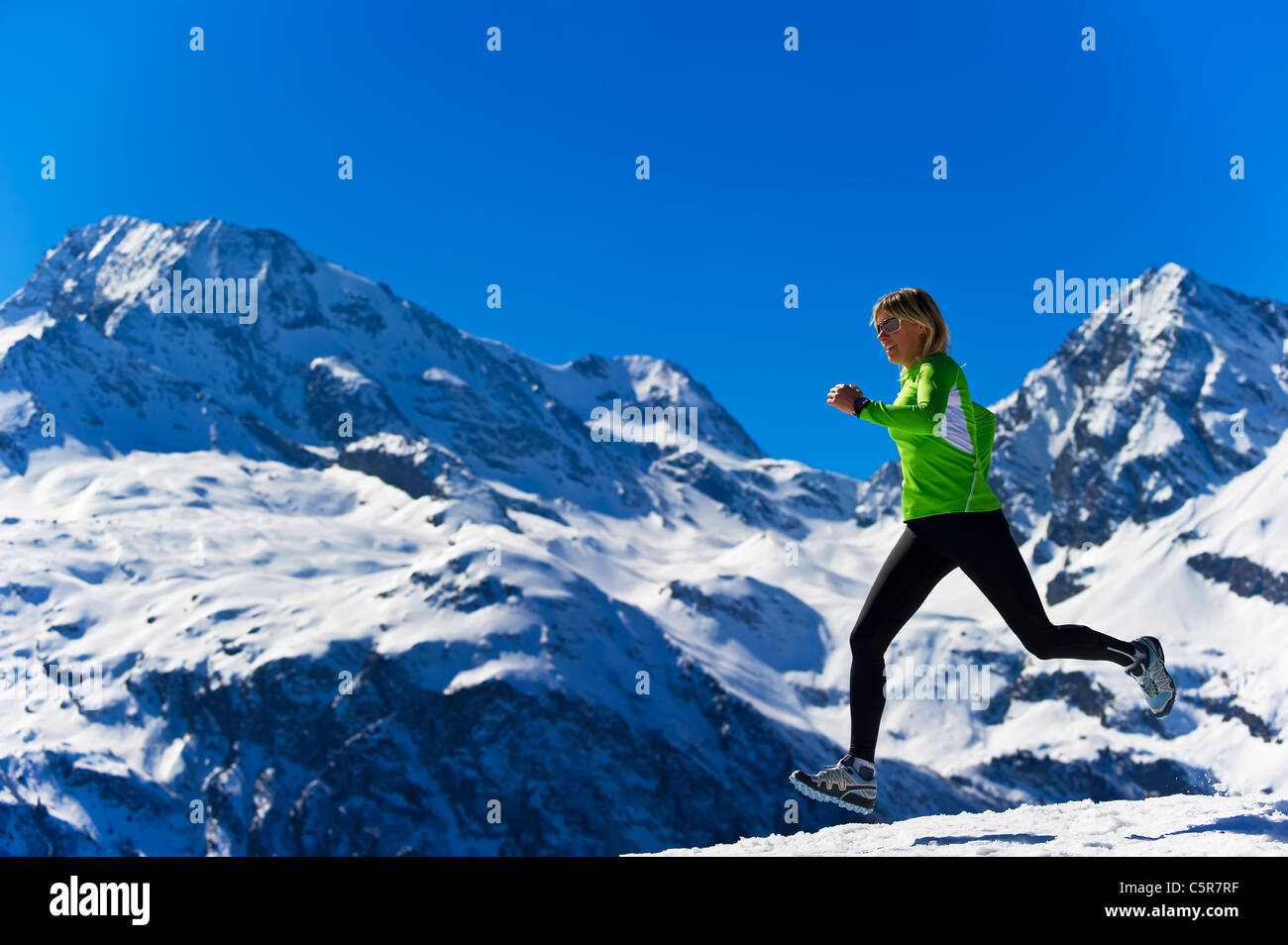 A women jogging across snowy alpine mountains. - Stock Image