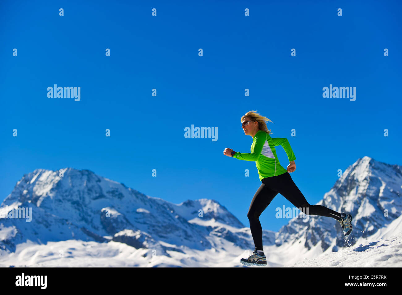 A woman jogging fast over snowy mountains. Stock Photo