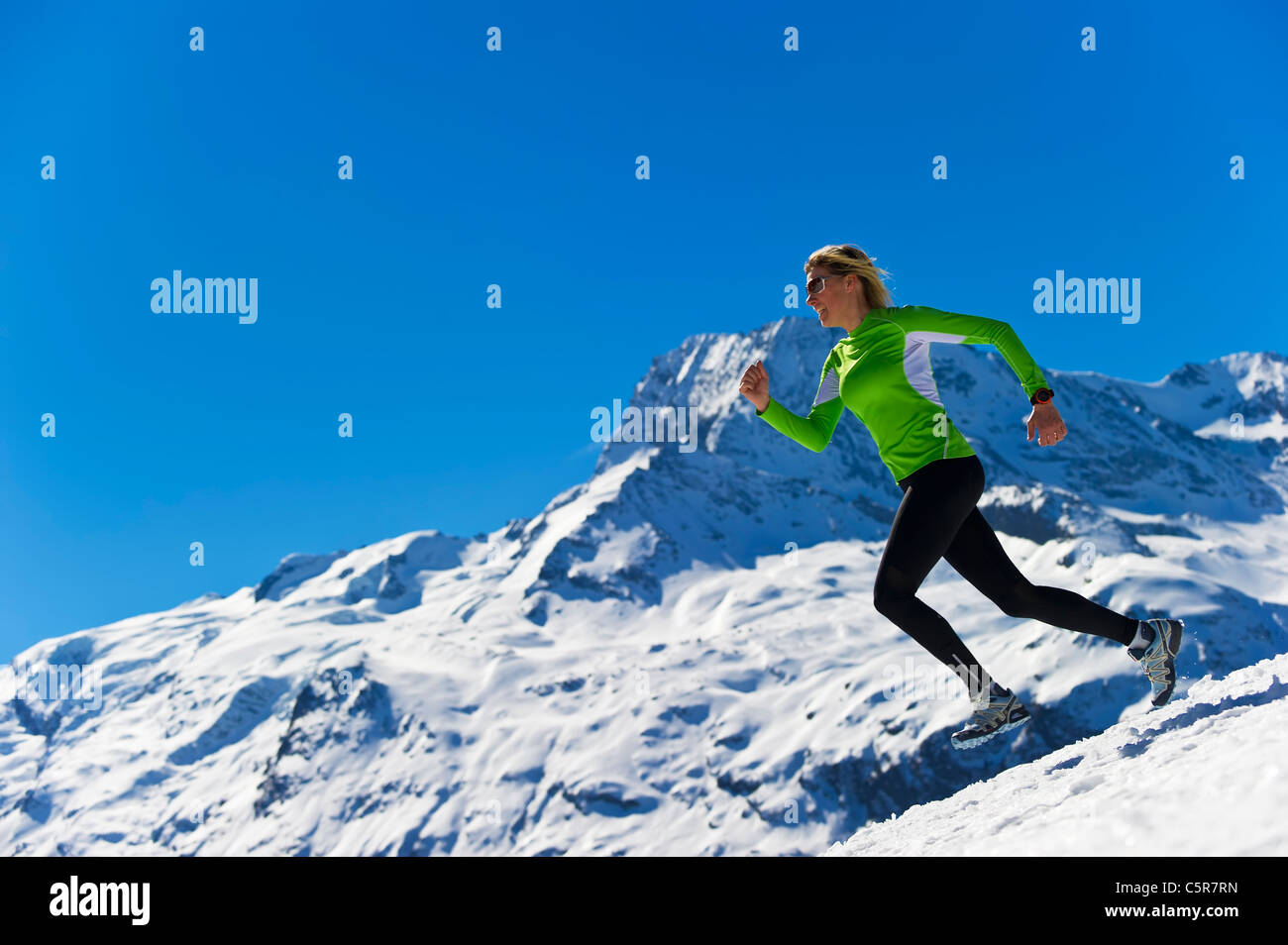 A woman jogging in high snowy alpine mountains. Stock Photo