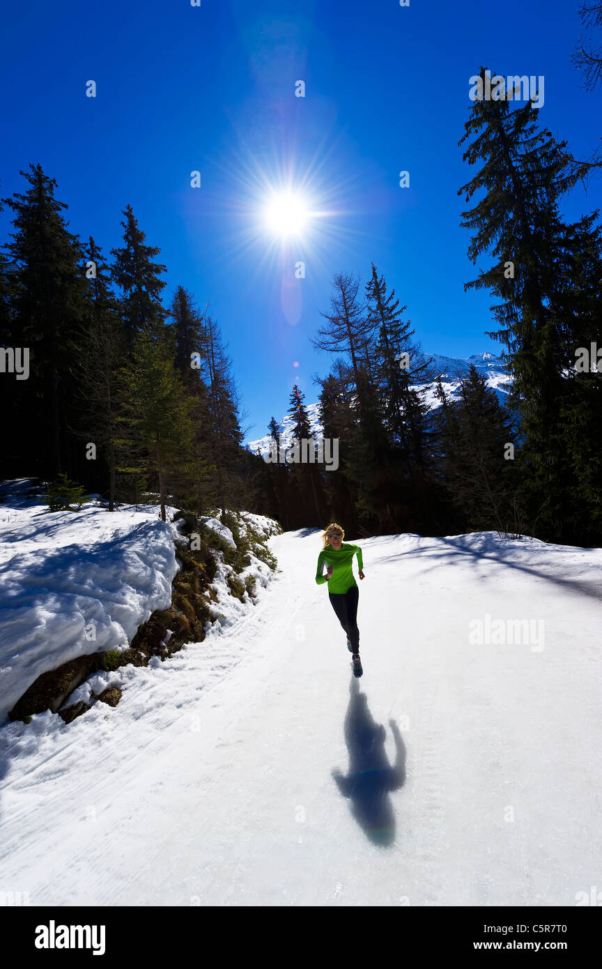 A girl jogging at high altitude in snowy mountains. - Stock Image