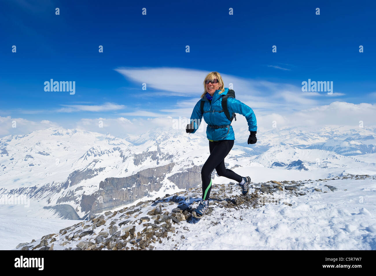 Women enjoying a run across a snowy alpine mountain range. - Stock Image