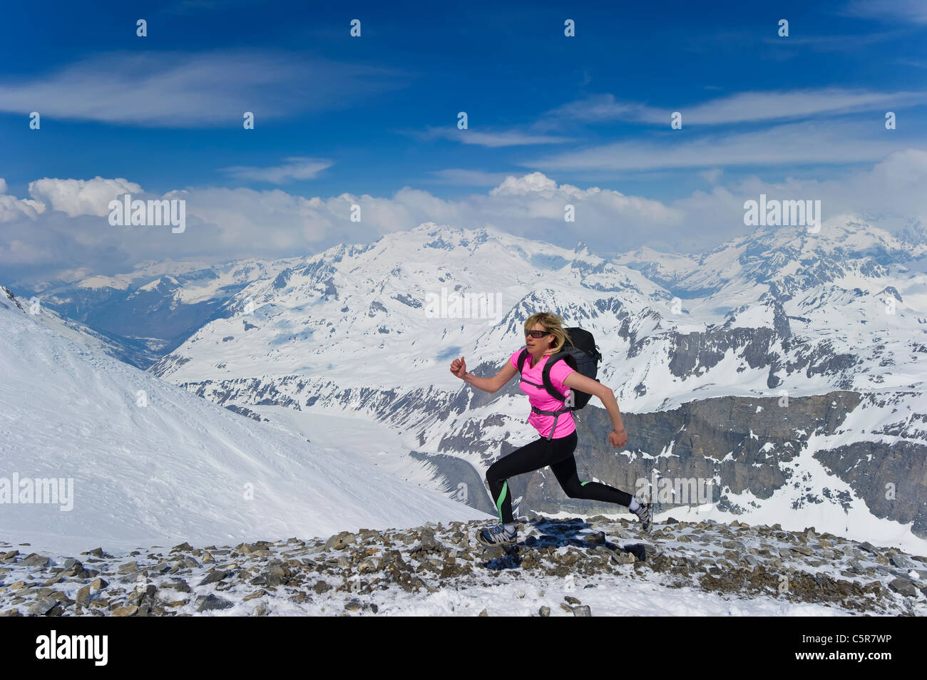 A woman running fast across snowy mountains. - Stock Image