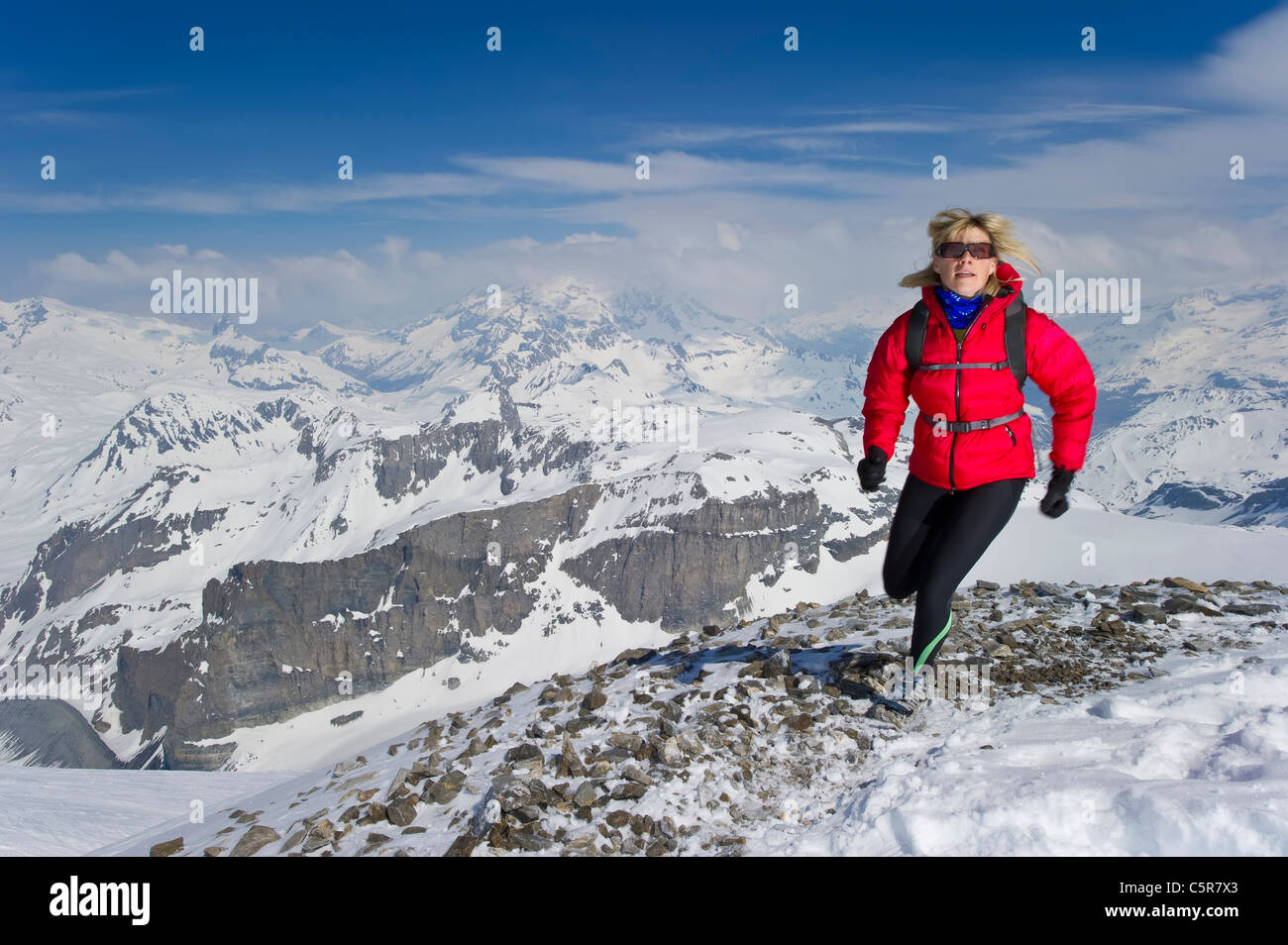Woman jogging over high snowy peaks. - Stock Image