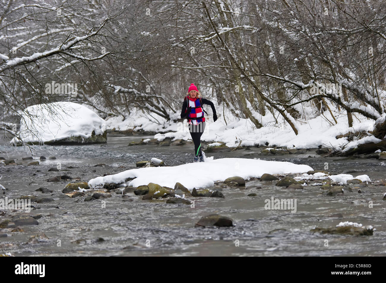 A jogger crossing a cold alpine river. - Stock Image