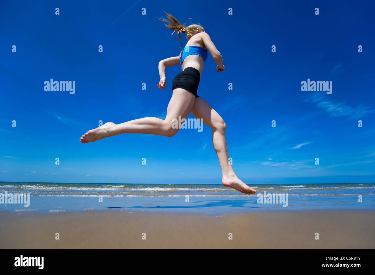 Jogging along a sandy beach at the oceans edge. - Stock Image