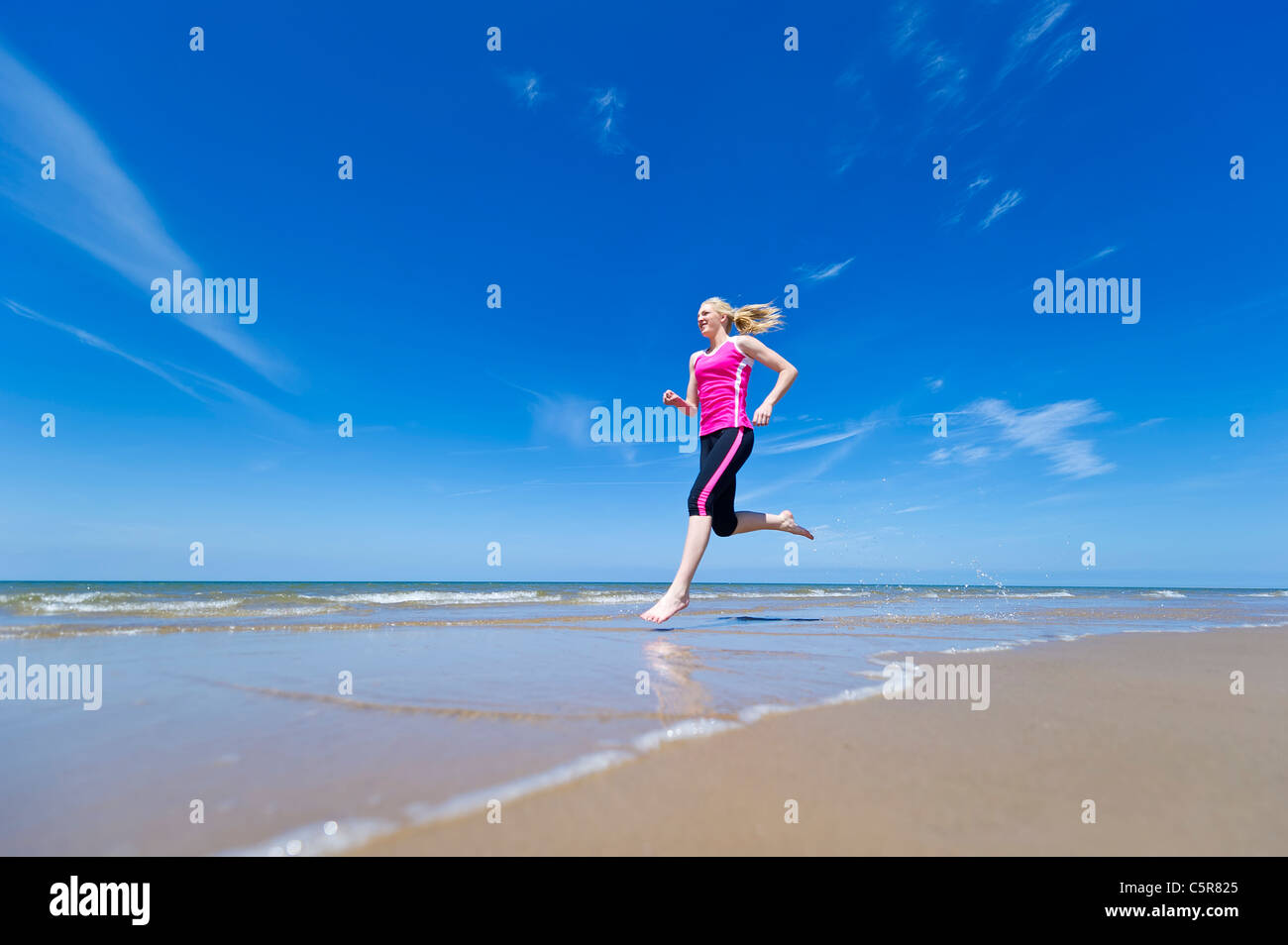 Jogging along the oceans edge. - Stock Image