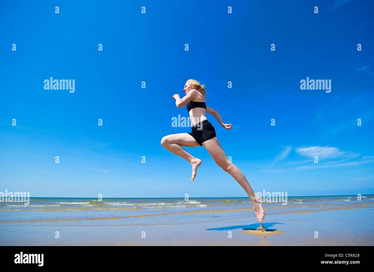An jogger running along a beach - Stock Image