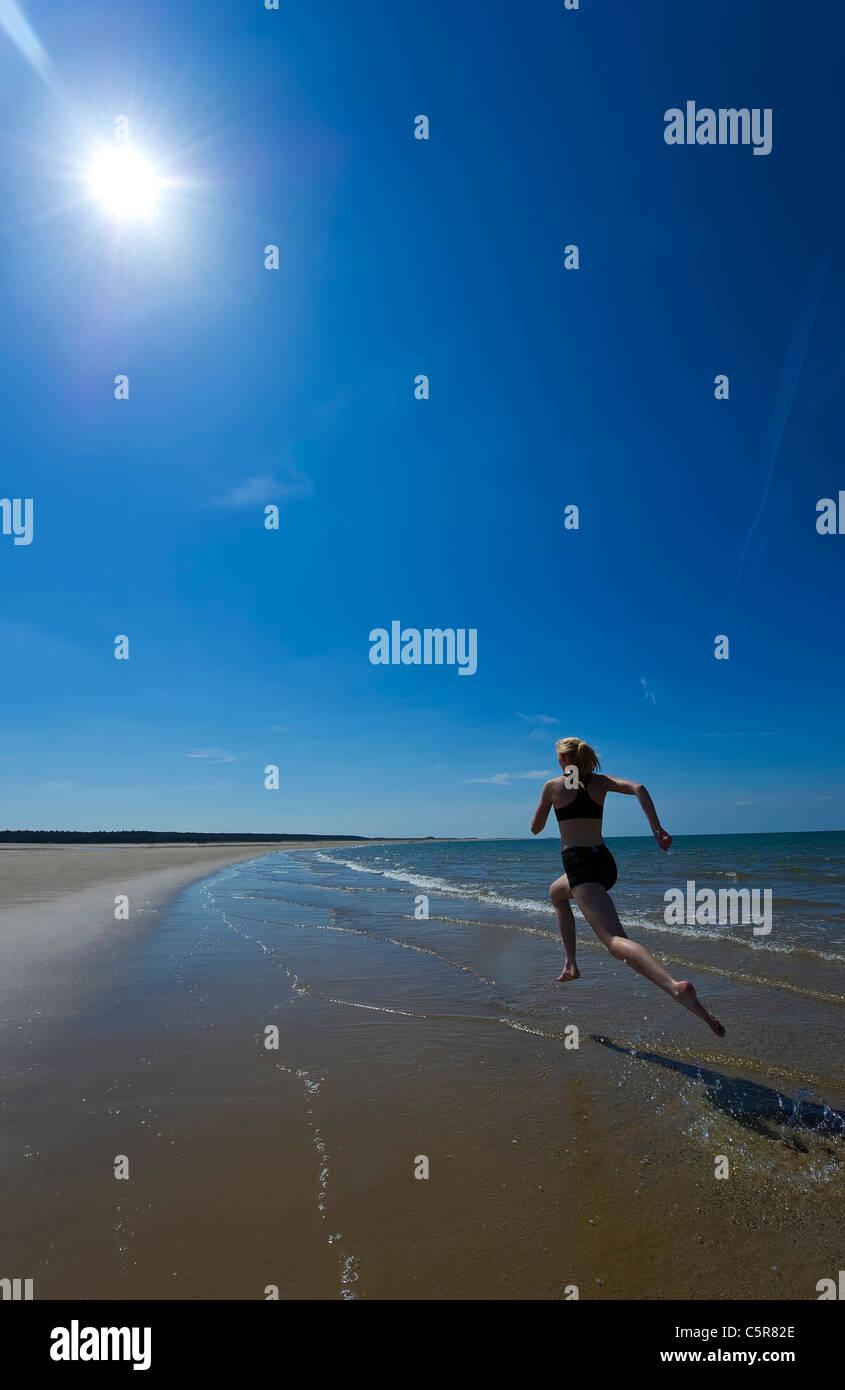 A jogger splashing along the ocean beach. - Stock Image