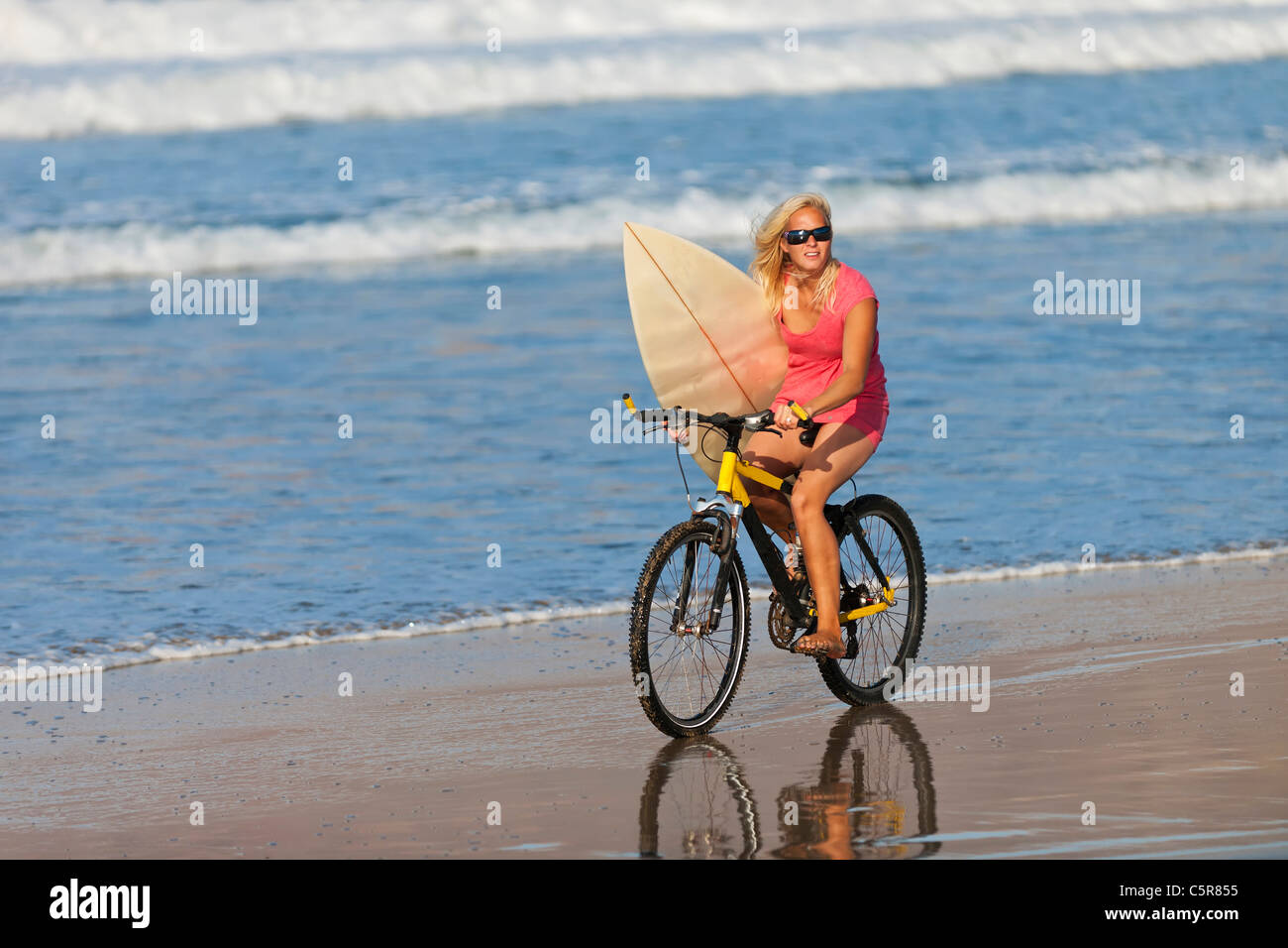 A surfer riding a mountain bike to the ocean. - Stock Image