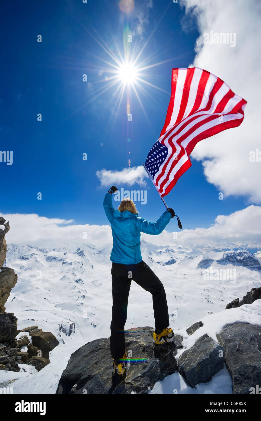 An American mountaineer punches the this air and celebrates on top of the World. - Stock Image