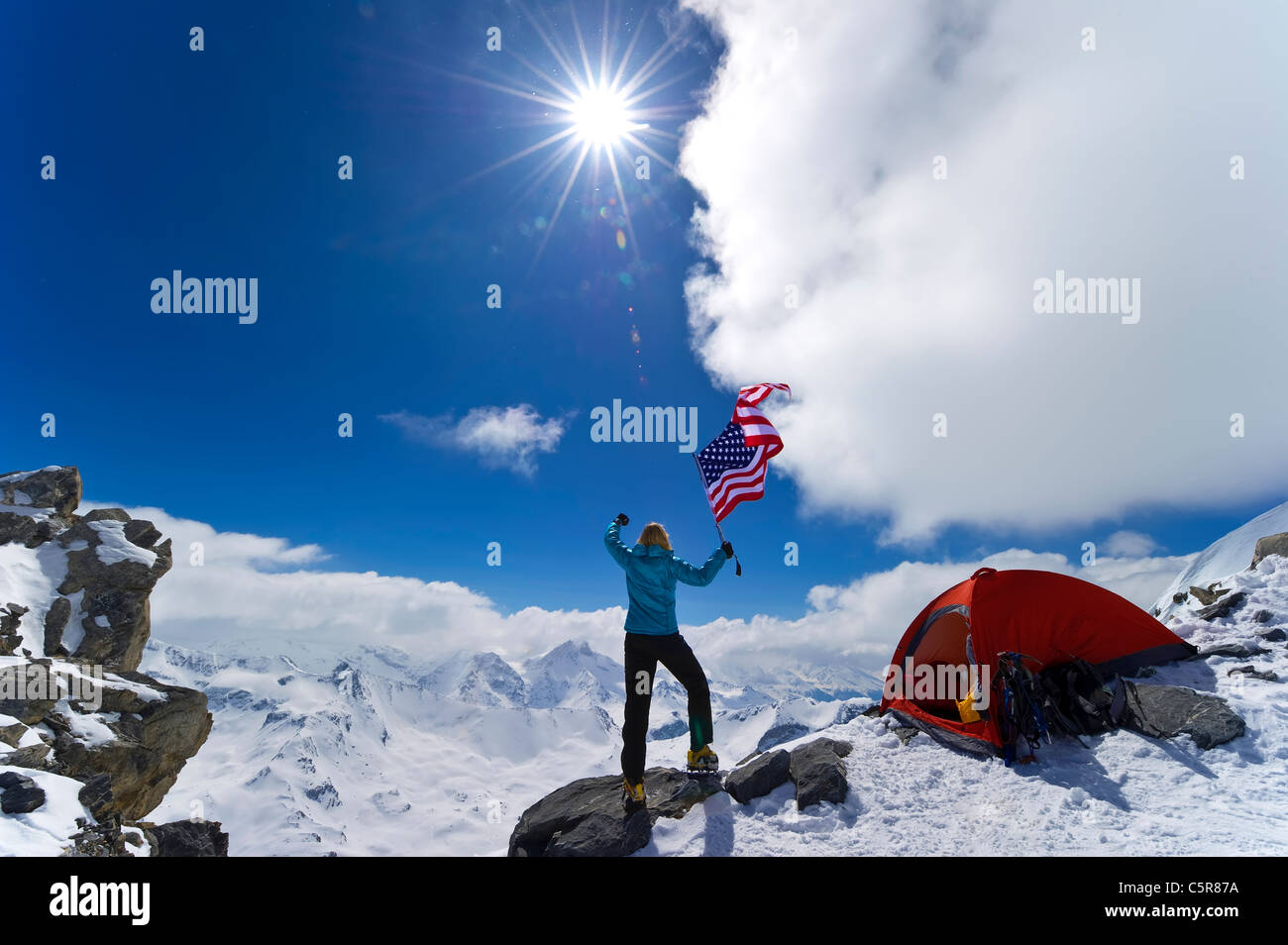 Mountaineer celebrates waving the stars and stripes. - Stock Image