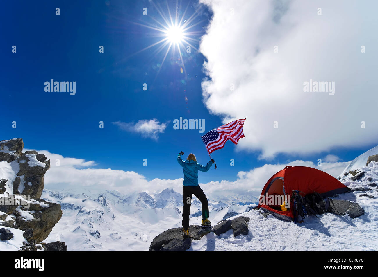 Climber celebrates on top of snowy mountain. - Stock Image