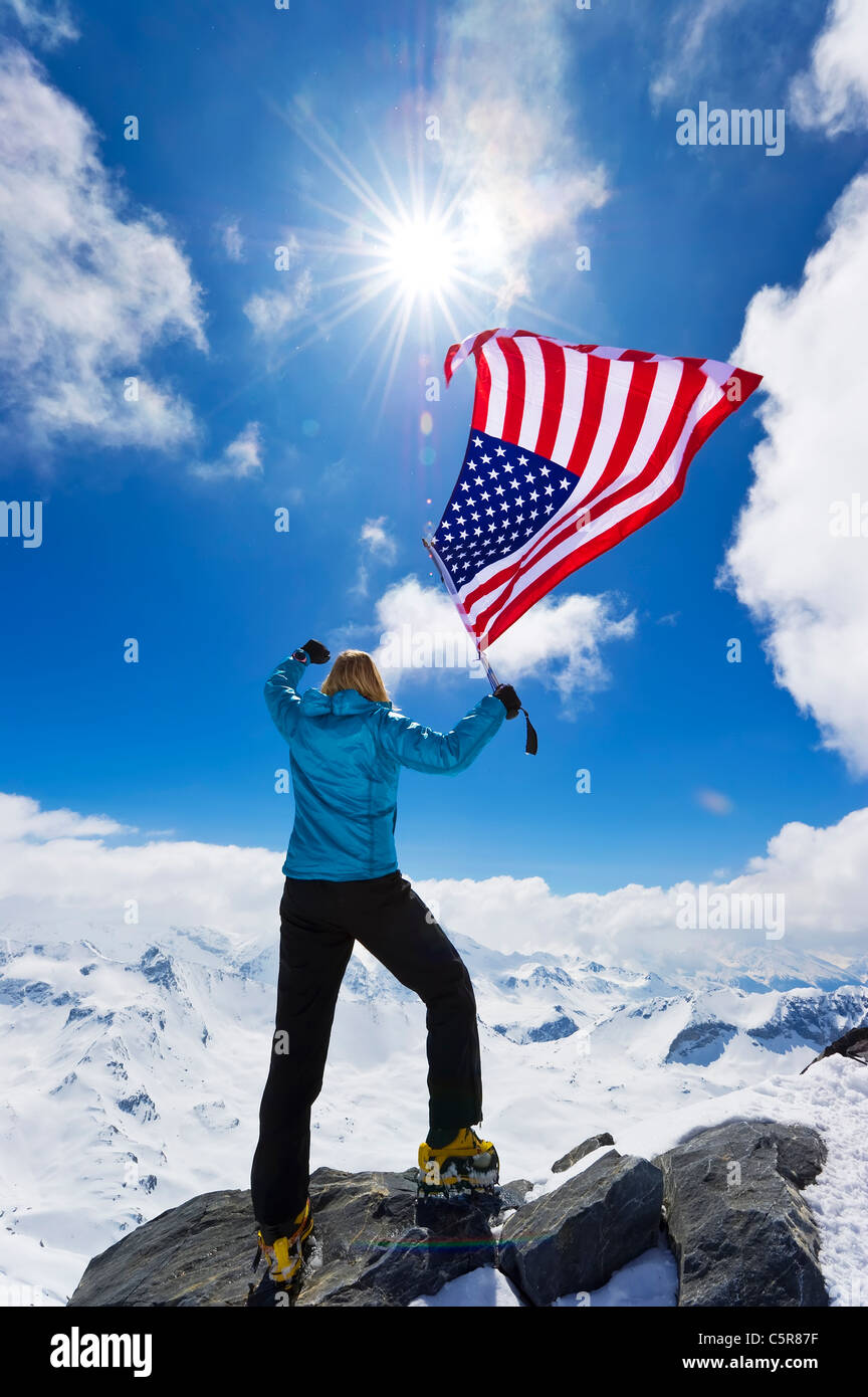 Mountaineer celebrates on summit. - Stock Image