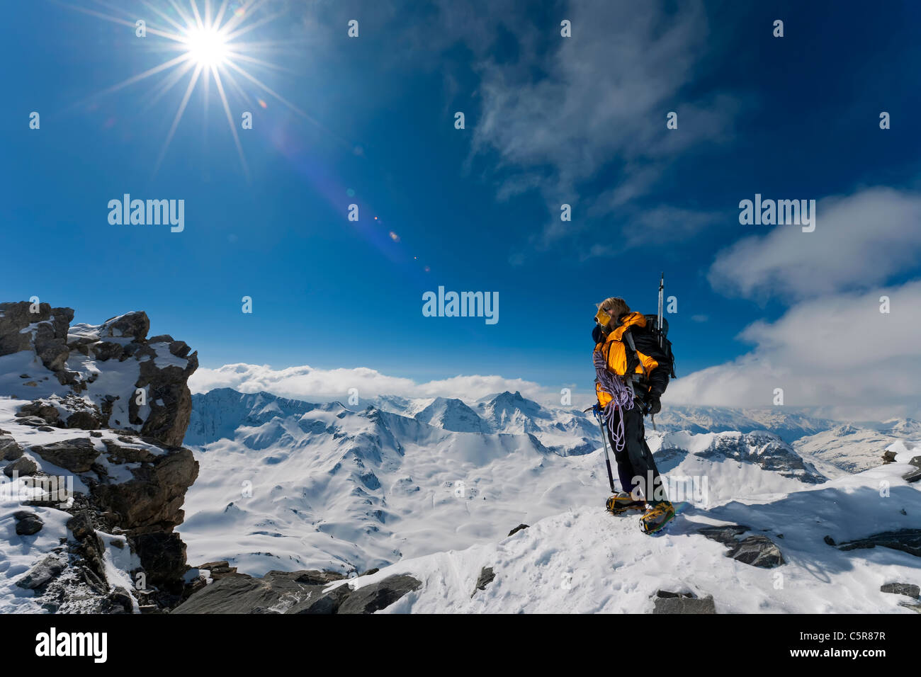 A mountaineer above the peaks and clouds looks at the amazing view. - Stock Image