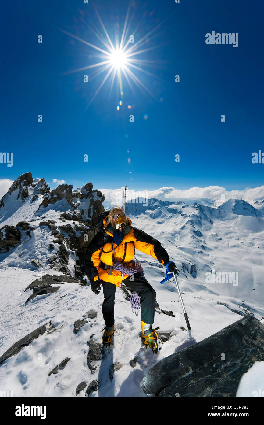 A mountaineer on climb to summit of snowy mountain high above the clouds, summits and peaks. - Stock Image