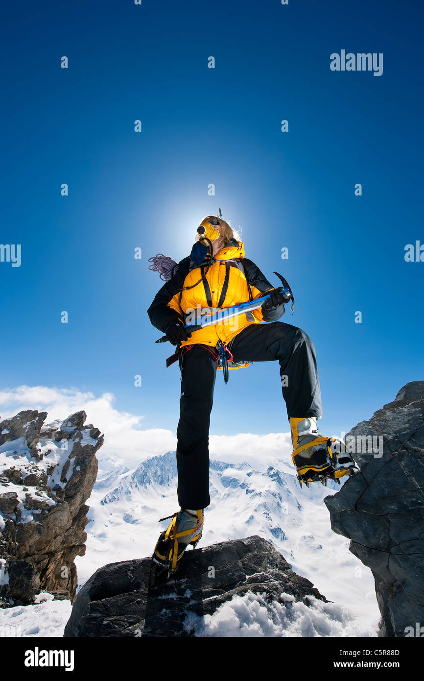 Female Mountaineer stands high above the peaks with oxygen mask, ice axes and crampons. - Stock Image