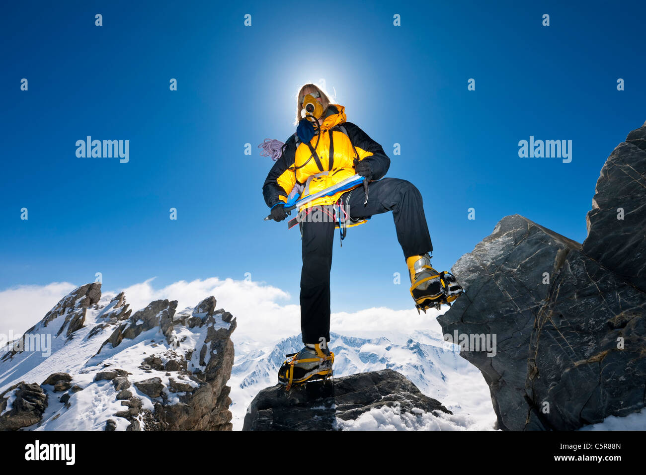 Mountaineer on snowy summits above the clouds. Stock Photo