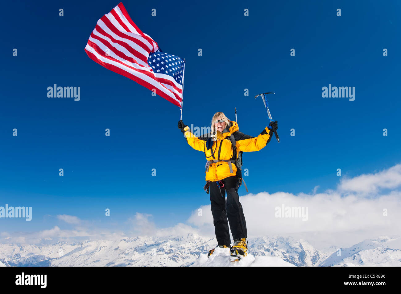 Mountaineer celebrates on summit flying the stars and stripes. - Stock Image