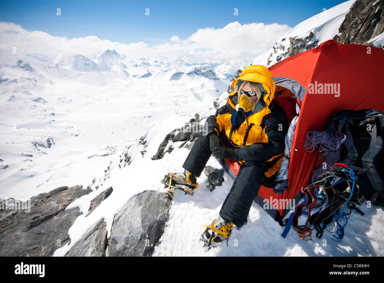A mountaineer sitting in tent with oxygen mask on at very high altitude. - Stock Image