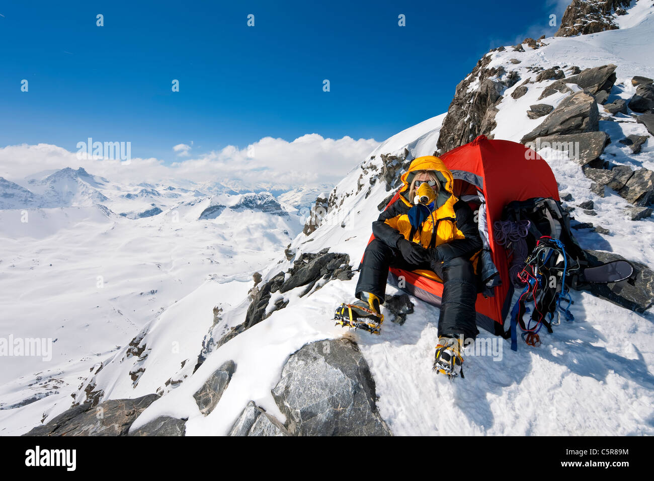 A climber in tent at very high altitude with oxygen breathing appartus. - Stock Image