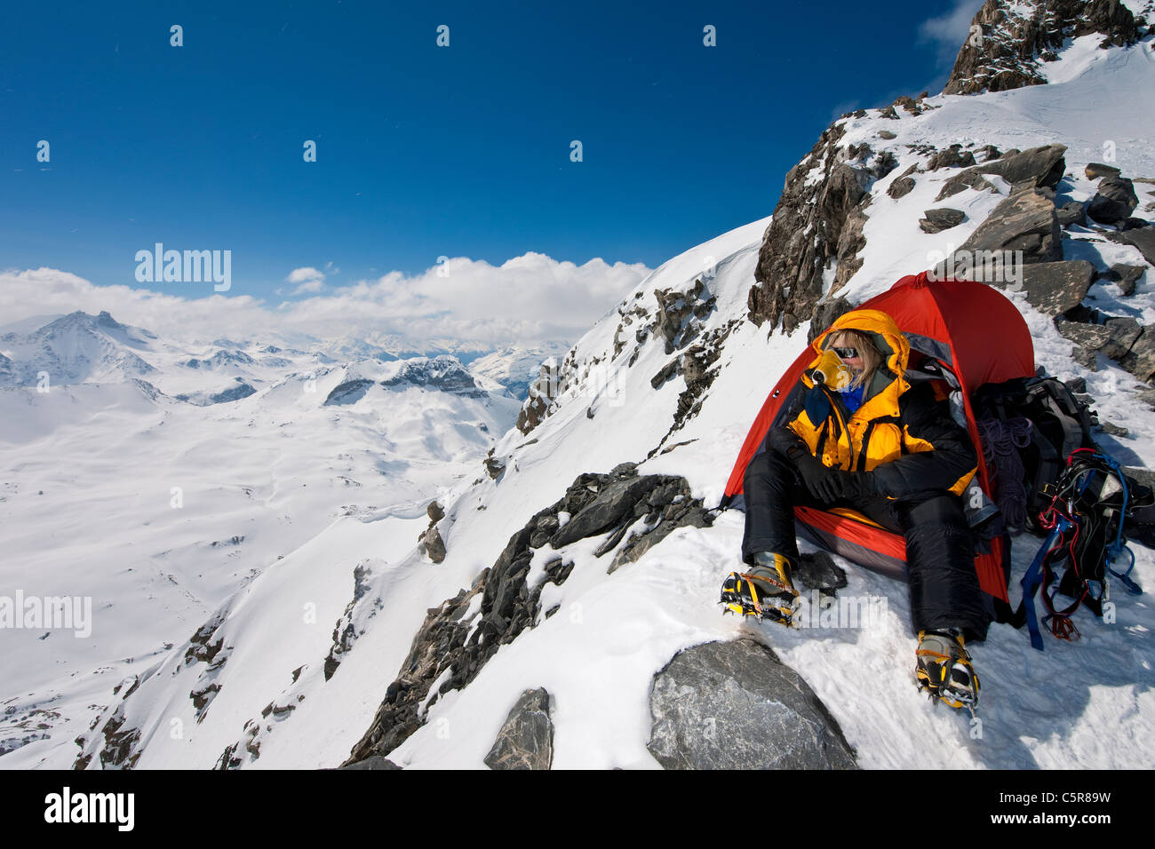 A mountaineer sitting in tent with oxygen mask looks out over high snowy mountains. - Stock Image
